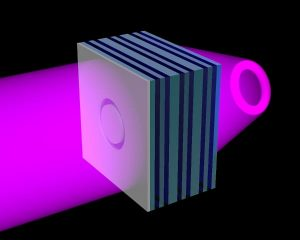 A NIST team has created an ultraviolet (UV) metamaterial formed of alternating nanolayers of silver (green) and titanium dioxide (blue). The metamaterial has an angle-independent negative refractive index, enabling it to act as a flat lens. When illuminated with UV light (purple) a sample object of any shape placed on the flat slab of metamaterial is projected as a three-dimensional image in free space on the other side of the slab. Here a ring-shaped opening in an opaque sheet on the left of the slab is replicated in light on the right. Bottom left: Scanning electron micrograph of a ring-shaped opening in a chromium sheet located on the surface of a flat slab of metamaterial. Bottom right: Optical micrograph of the image projected beyond the slab under UV illumination, demonstrating that the metamaterial slab acts as a flat lens. Image: Lezec/NIST.
