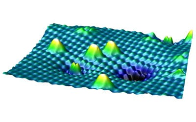 An STM image of the surface of titanium dioxide with different forms of oxygen. The higher, white peaks are oxygen molecules that are sitting on the surface, the smaller double peak in the foreground is an oxygen molecule that is already embedded. Image: M. Setvin et al. / AAAS
