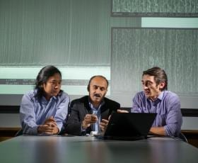 (Left to right) Georgia Tech Ph.D. student Wei Chen, Professor Suresh Sitaraman and Ph.D. student Nick Ginga examine a carbon nanotube sample against a backdrop of scanning electron microscope images of carbon nanotubes. Image: Georgia Tech/Rob Felt.