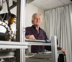 Walt de Heer, a Regent's professor in the School of Physics at the Georgia Institute of Technology, poses with equipment used to measure the properties of graphene nanoribbons. De Heer and collaborators from three other institutions have reported ballistic transport properties in graphene nanoribbons that are about 40 nanometers wide. Image: Georgia Tech/Rob Felt.