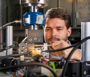 Sandia National Laboratories researcher Brad Salzbrenner tests laser-welded objects in pure tension, shear and mixed tension-shear loading. One pilot study in Sandia's long-term Predicting Performance Margins program involves laser welds, which are widely used in engineered systems. Image: Randy Montoya.
