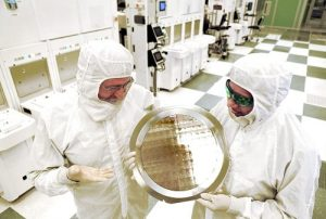 SUNY College of Nanoscale Science and Engineering's Michael Liehr, left, and IBM's Bala Haranand look at wafer comprised of 7nm chips on Thursday, July 2, 2015, in a NFX clean room Albany.   Several 7nm chips at SUNY Poly CNSE on Thursday in Albany.  (Darryl Bautista/Feature Photo Service for IBM)
